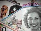 """Una mujer grafitera y activista pinta una parte de un mural de diez metros de altura con la imagen de Marielle Franco, entre los edificios de un barrio de la ciudad de Sao Paulo (Brasil). """"Marielle vive"""" es el lema inscrito sobre la gran escalera de cemento que lleva el nombre de la concejala Marielle Franco, una obra homenaje que continúa la batalla que ella lideró hasta que fue asesinada, hace hoy once meses."""