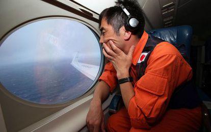 Koji Kubota, um salva-vidas japonês, observa o oceano em um Gulfstream V em busca do MH370.