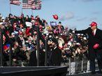 El presidente Donald Trump arroja gorras a sus seguidores durante un mitin en el aeropuerto de Scranton, Pensilvania, el lunes.