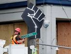 "A worker removes a ""Black Lives Matter St."" sign from a Seattle police precinct Wednesday, July 1, 2020, in Seattle, where streets had been blocked off in an area demonstrators had occupied for weeks. Seattle police showed up in force earlier in the day at the ""occupied"" protest zone, tore down demonstrators' tents and used bicycles to herd the protesters after the mayor ordered the area cleared following two fatal shootings in less than two weeks. The ""Capitol Hill Occupied Protest"" zone was set up near downtown following the death of George Floyd while in police custody in Minneapolis. (AP Photo/Elaine Thompson)"