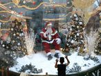 Abilio Nunes, a Santa Claus performer, waves to children from inside a bubble, a protective measure against the spread of COVID-19, at a shopping center in Brasilia, Brazil, Wednesday, Dec. 16, 2020. (AP Photo/Eraldo Peres)