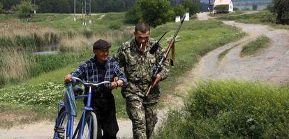 Um rebelde pró-russo ajuda um homem em Slaviansk.