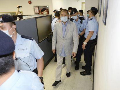 O empresário Jimmy Lai, no centro, escoltado pela polícia na redação do 'Apple Daily', nesta segunda-feira, em Hong Kong.