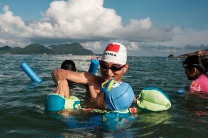 Uma banhista, com uma touca de natação com a bandeira da China, ajuda uma criança a usar uma boia na praia de Dongchong.