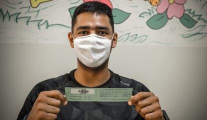 Andrei Wesley Monteiro mostra o cartão de vacinação.