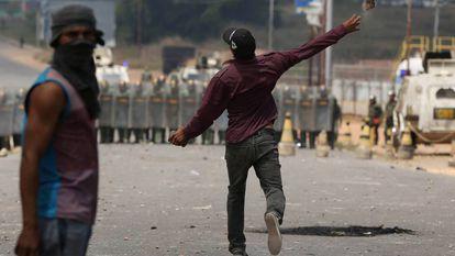 Venezuelanos em solo brasileiro atiram pedras contra soldados da Guarda Nacional Bolivariana