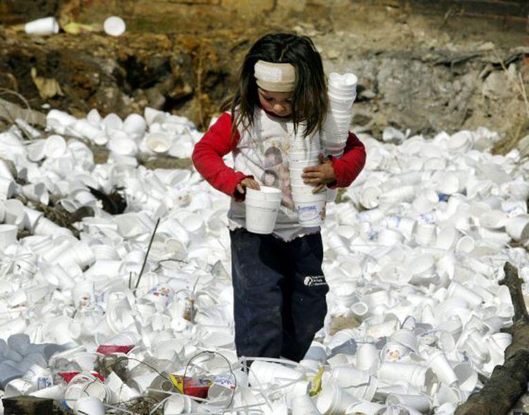 Menina recolhe copos de plástico em um lixão.