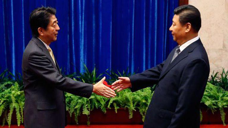 Abe (esq), primeiro-ministro japonês, cumprimenta Xi.