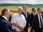Belarus President Alexander Lukashenko, second left, stands on the field as he visits the Novaya Zhizn (New Life) agricultural enterprise in the Nesvizh district, Belarus, Monday, July 27, 2020. The presidential election in Belarus is scheduled for Aug. 9, 2020. (Andrei Stasevich/BelTA Pool Photo via AP)