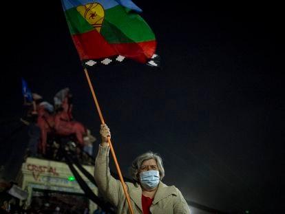 """Mulher com a bandeira mapuche celebra a vitória do """"aprovo"""" no plebiscito para a redação de uma nova Constituição no Chile."""