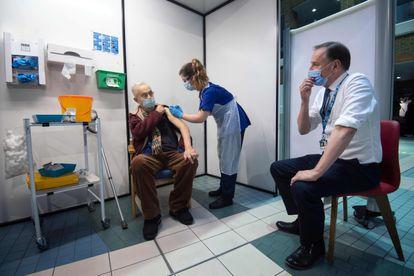O diretor do Serviço Nacional de Saúde do Reino Unido, Simon Stevens, observa um paciente receber a vacina da Pfizer, nesta terça-feira, no Hospital Guy, em Londres.