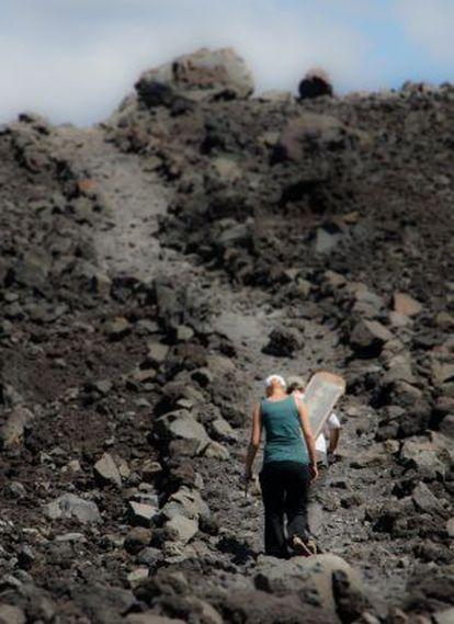Dois turistas escalam o vulcão Cerro Negro.