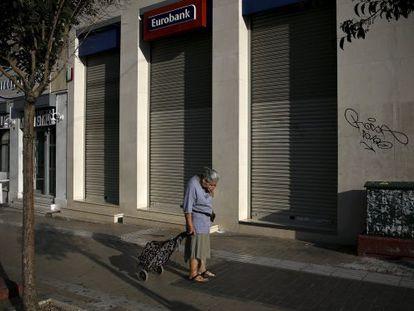 Uma mulher passa adiante de uma sucursal bancária fechada, na segunda-feira em Atenas.