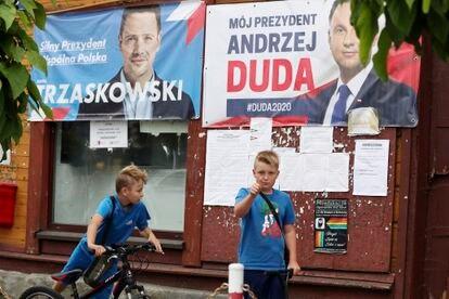Garotos em frente a cartazes dos candidatos Andrzej Duda e Rafal Trzaskowski, na cidade de Raciaz.