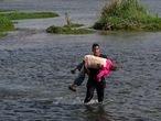 Un migrante venezolano cruza el Río Bravo con una mujer de la tercera edad en brazos el 26 de mayo.