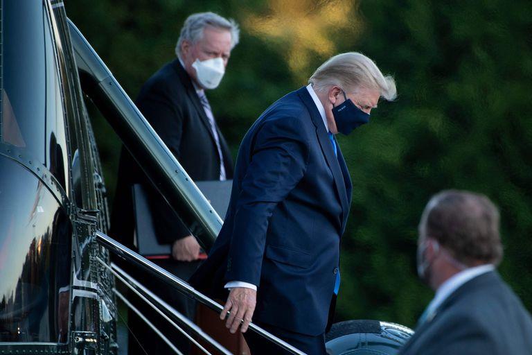 O Chefe de Gabinete da Casa Branca, Mark Meadows (à esquerda), observa o presidente Donald Trump deixar o Marine One ao chegar ao Walter Reed Medical Center em Bethesda, em 2 de outubro de 2020.