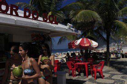 Banhistas tomam coco no calçadão da praia de Ipanema.