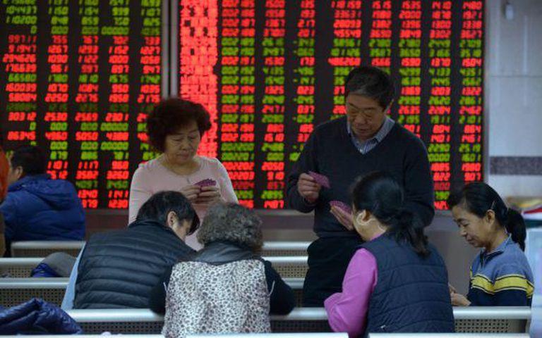 Investidores jogam baralho numa corretora de títulos em Pequim.
