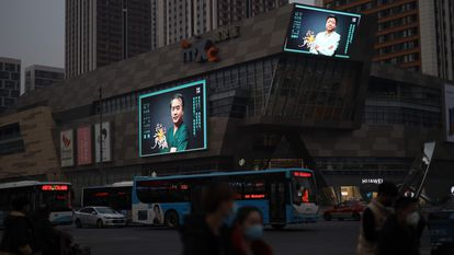 Uma rua da cidade chinesa de Shenyang, nesta quarta-feira. Nas telas, um programa de homenagem aos médicos que viajaram a Wuhan.