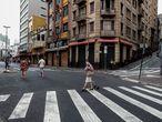 AME6695. SAO PAULO (BRASIL), 26/12/2020.- Personas pasan frente a tiendas cerradas por un nuevo confinamiento debido al coronavirus hoy, en la calle 25 de marzo el mayor centro del comercio popular de la ciudad de Sao Paulo (Brasil). Brasil cumple este sábado diez meses desde su primer caso de coronavirus y celebrará el fin de año bajo una estricta cuarentena en buena parte de su territorio, en momentos en que la pandemia vuelve a acelerarse en un país que ya registra 190.500 decesos por el patógeno. EFE/Sebastiao Moreira