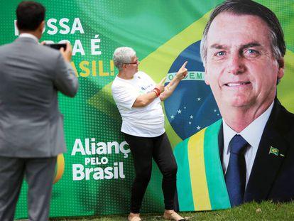 Apoiadora posa em frente a banner que promove o Aliança pelo Brasil.