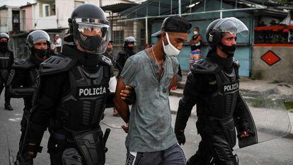 Policiais conduzem um homem detido nos protestos sociais em Cuba, em Havana, em 13 de julho.