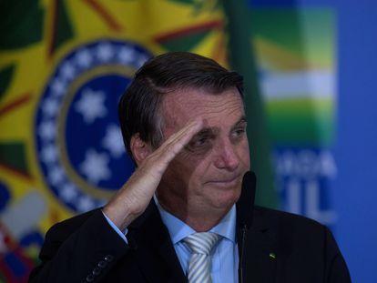 O presidente Bolsonaro faz uma saudação militar após sancionar a lei de autonomia do Banco Central.