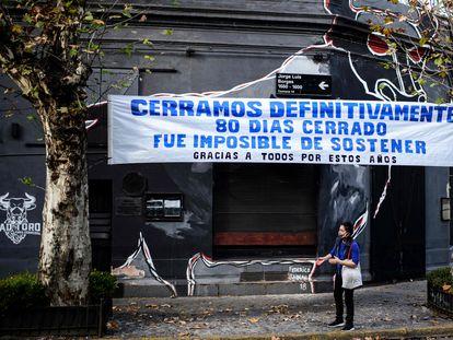 Um comércio fechado durante a pandemia em Buenos Aires exibe uma faixa de protesto na fachada.