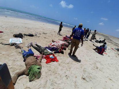 Trabalhadores da OIM e forças de segurança do Djibuti ao lado dos corpos dos migrantes que morreram na segunda-feira quando tentavam regressar ao continente africano.