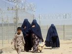 Afghan women clad in burqas and a child walk next to a fence as they cross into Pakistan via Friendship Gate crossing point in the Pakistan-Afghanistan border town of Chaman, Pakistan September 4, 2021. REUTERS/Abdul Khaliq Achakzai NO RESALES. NO ARCHIVE