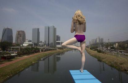 """Uma estátua de uma mulher em um trampolim em uma ponte do rio Pinheiros. Batizada de """"As Margens do Rio Pinheiros"""", a intervenção do artista plástico de Eduardo Srur alerta para a poluição."""
