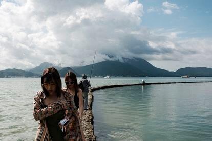 Turistas chinesas são vistas caminhando em um muro artificial, na praia de Dapeng Jiaochangwei.
