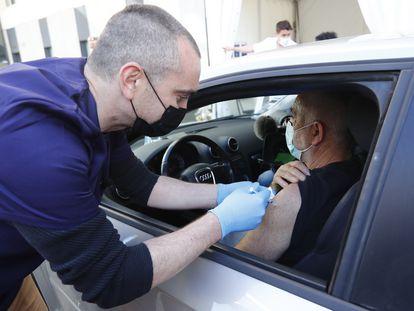 Um agente da saúde vacina um homem em seu carro em Saint-Jean-de-Vedas, próximo a Montpellier (França).