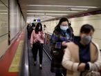People wearing face masks use the staircase at a subway station, following the outbreak of coronavirus disease (COVID-19) in Beijing, China, March 27, 2020. REUTERS/Carlos Garcia Rawlins