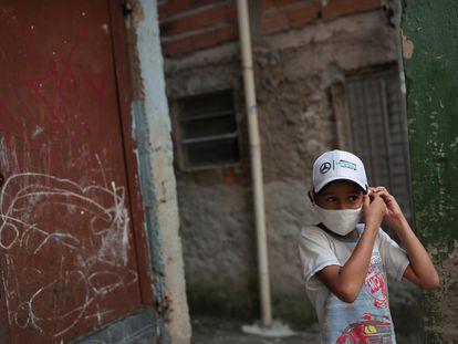 Criança ajusta máscara na favela de Paraisópolis, em São Paulo.
