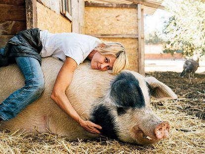 Laura Luelmo, responsável pelo santuário de animais da fazenda Wings of Heart, em Madri, e o porco Baku.