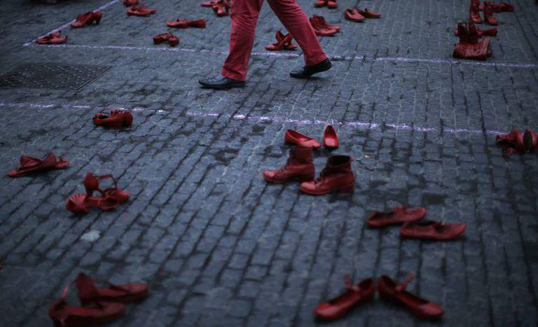 Um homem caminha entre sapatos femininos em um protesto contra a violência machista em Barcelona (Espanha), na segunda-feira.