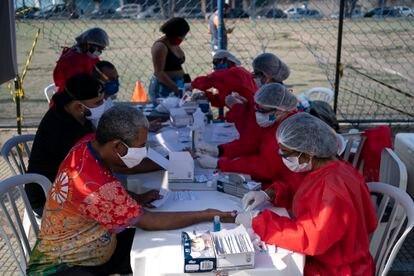 Uma profissional de saúde recolhe uma amostra de sangue de um homem para um teste de covid-19 em Duque de Caxias.