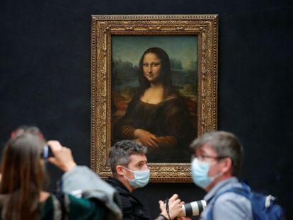 Jornalistas em frente ao quadro 'Mona Lisa', no Louvre, que prepara reabertura, na terça-feira.