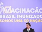 Brazilian President Jair Bolsonaro gestures during the launch of the  national vaccination plan against the novel coronavirus Covid-19 at Planalto Palace in Brasilia, on December 16, 2020. - The government has not released a date for the start of the vaccination but commits to start the process 5 days after the approval of a vaccine by the health agency (ANVISA) and expects to take 12 to 16 months to vaccinate the entire Brazilian population. (Photo by EVARISTO SA / AFP)