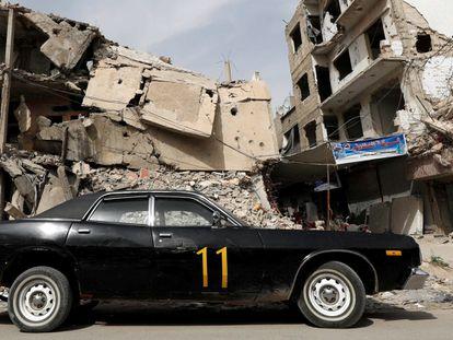 Carro estacionado diante de edifício em ruínas, nesta terça-feira em Duma, na periferia de Damasco.
