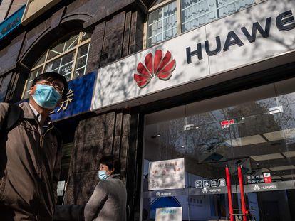 Nesta foto de arquivo, tirada em 22 de abril, pessoas passam diante de uma loja da Huawei em Pequim.