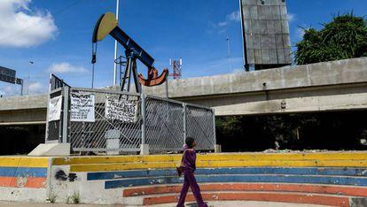 Mulher caminha diante de uma bomba de extração de petróleo na Universidade de Caracas