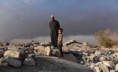 Salih Latif e um de seus filhos na montanha de escombros que restou de seu lar em Haji Ali.