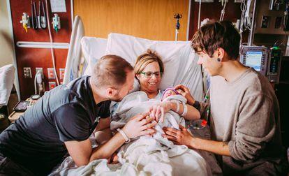 Cecile Eledge, após dar à luz Uma, entre seu filho Matthew (esq.) e o marido dele, Elliot.
