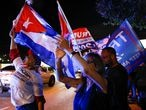 A supporter of U.S. President Donald Trump holds a Cuban flag during the 2020 U.S. presidential election, in Miami, Florida, U.S., November 3, 2020. REUTERS/Marco Bello TPX IMAGES OF THE DAY