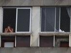 A man prays from his window as priest Jorge Luiz de Oliveira delivers the Angelus prayer from the balcony of the Santuario Basilica de Sao Sebastiao, following the coronavirus disease (COVID-19) outbreak, in Rio de Janeiro, Brazil May 6, 2020. REUTERS/Pilar Olivares
