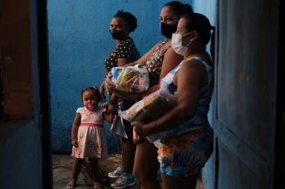 Moradoras de uma favela de Rio de Janeiro, após receber doações em uma escola, em abril.