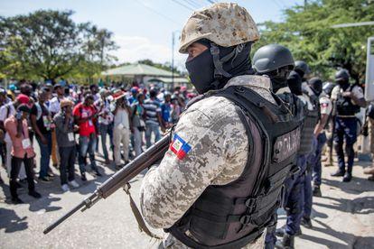 Policial armado vigia protesto de jornalistas em Porto Príncipe.