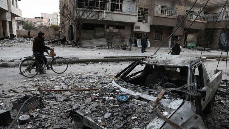 Sírios caminham entre destroços na localidade de Arbin, na região de Guta Oriental